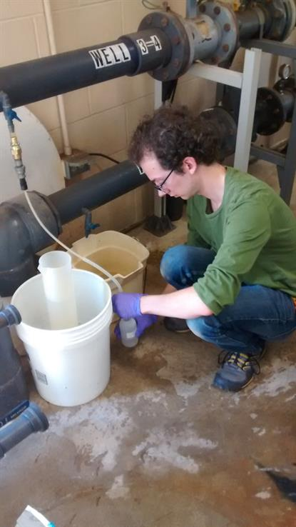 ISWS Employee Devin Mannix takes a well sample for water quality analysis, 2015